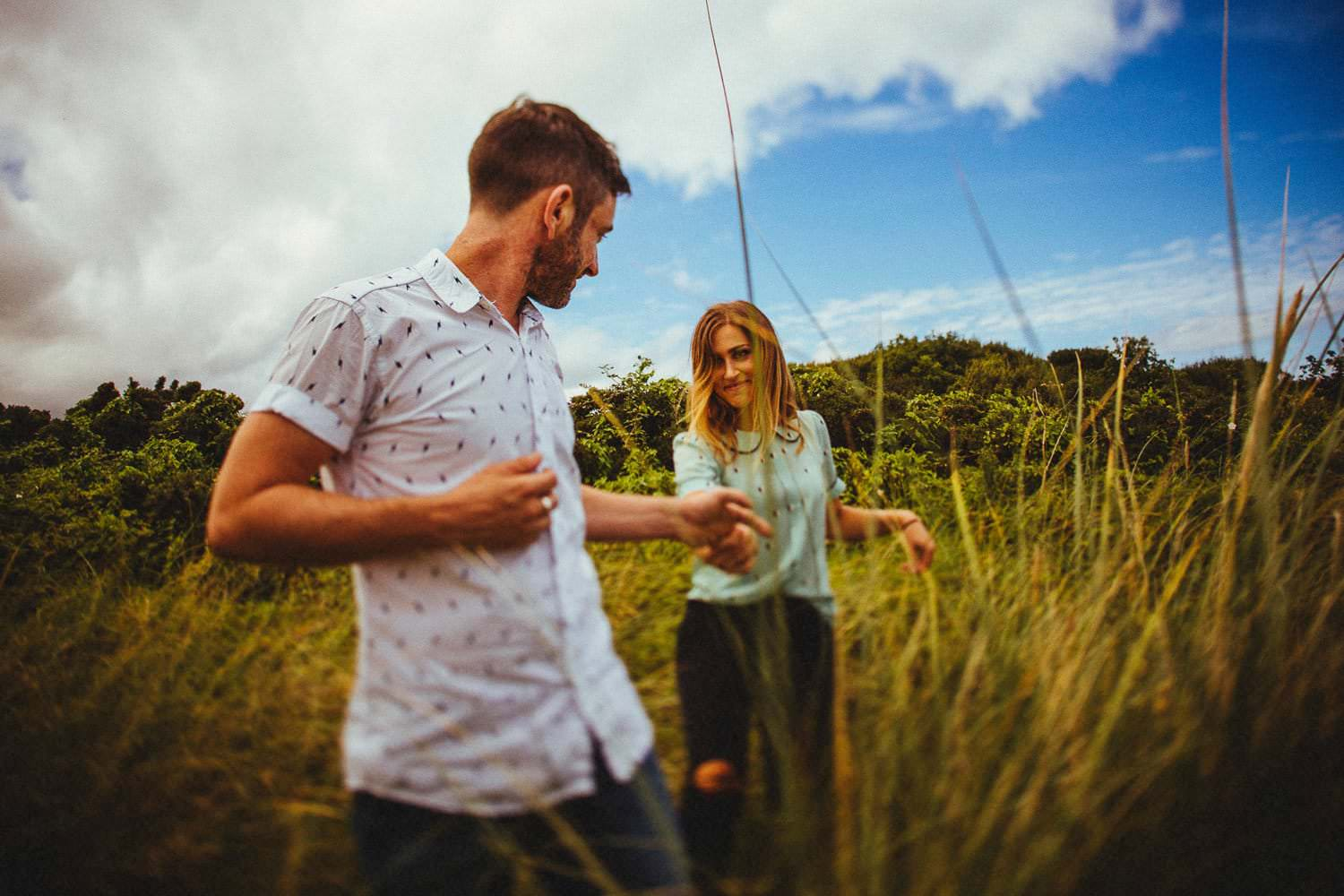 Couple run through tall grass during engagement shoot at Connor Pass