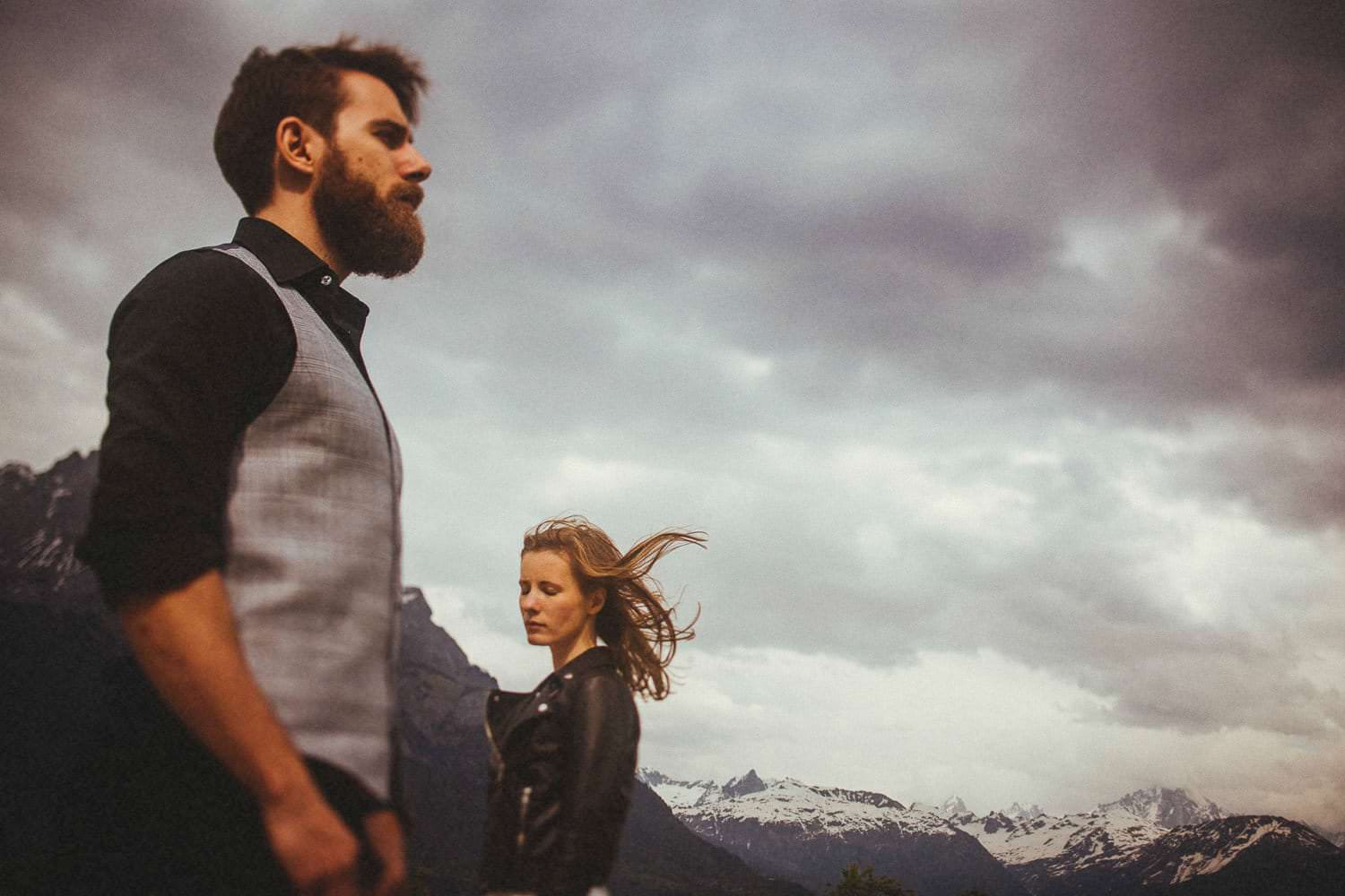 Husband and wife standing in front of the ice capped mountains in the French Alps while celebrating their anniversary with Magic the Photographer