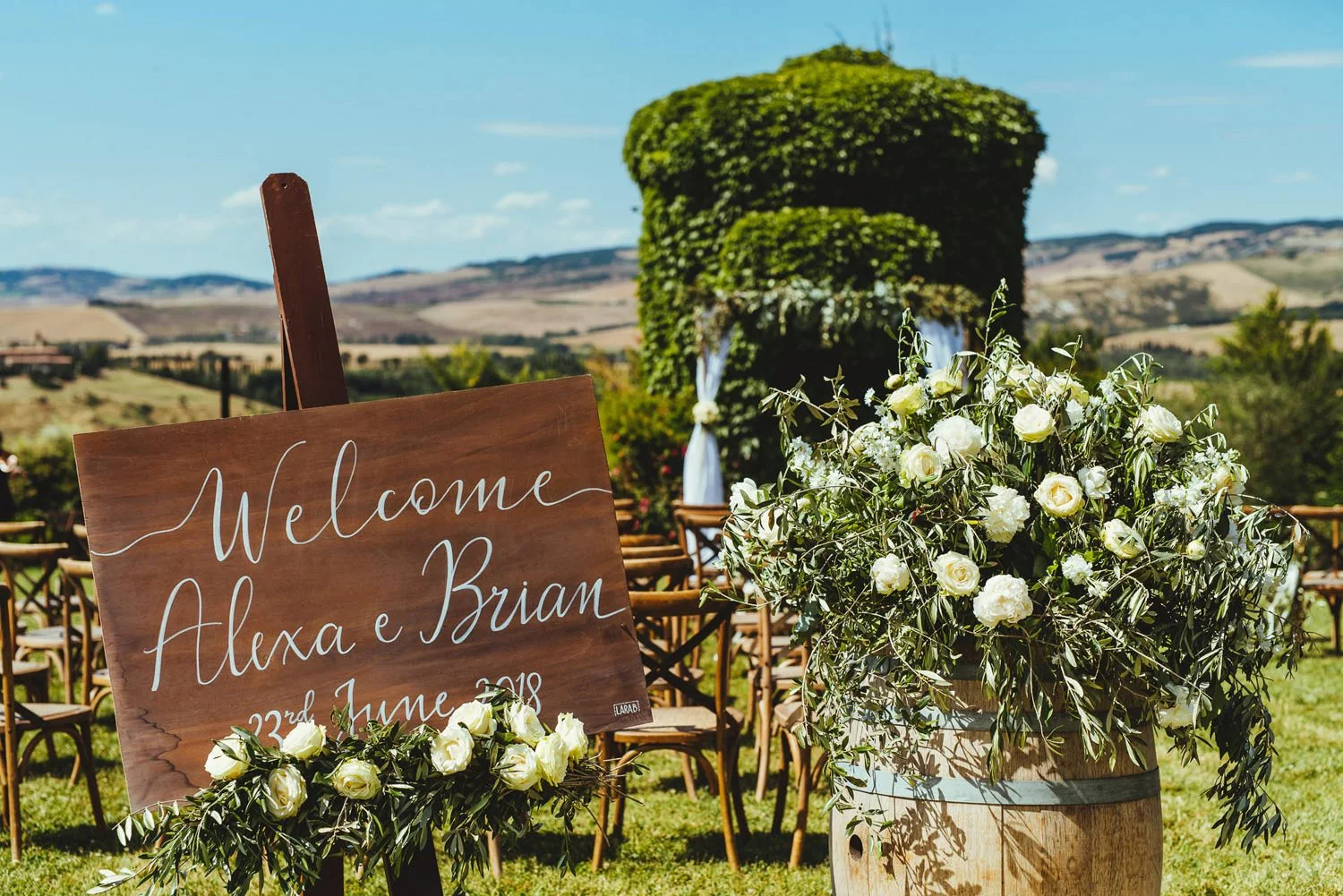 A sign reads 'Welcome Alexa e Brian' at a beautiful outdoor wedding ceremony in Tuscan.