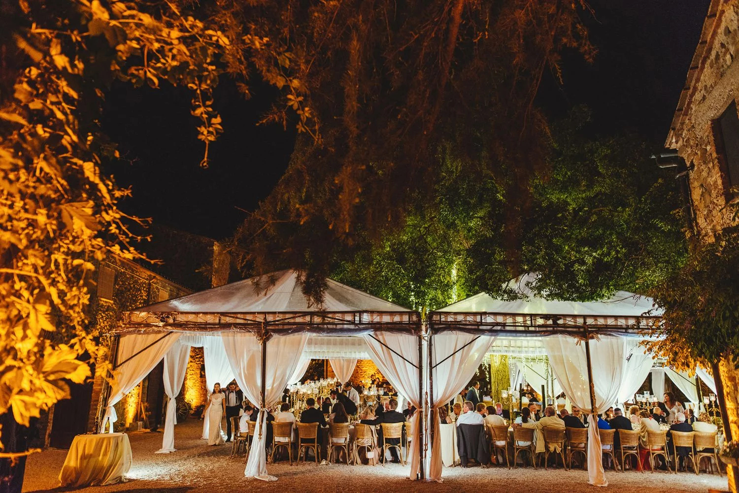 An outdoor wedding reception under decorated gazebos at Borgo Di Castelvecchio in Tuscany, Italy.