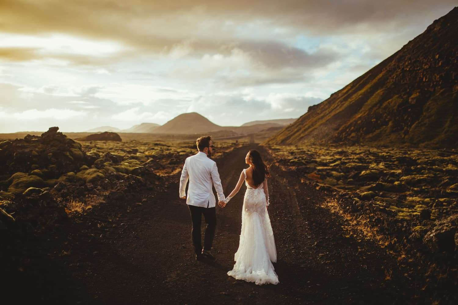 A newlywed bride and groom walk hand-in-hand down a dirt path in beautiful Iceland for wedding photos with Magic Wedding Photographer in Europe.
