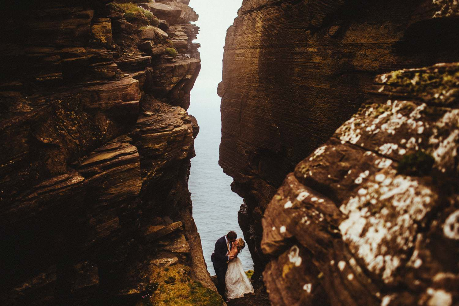 Bride and groom kissing between rocks at the Cliffs of Moher showing off one of the coolest places to elope in Europe.