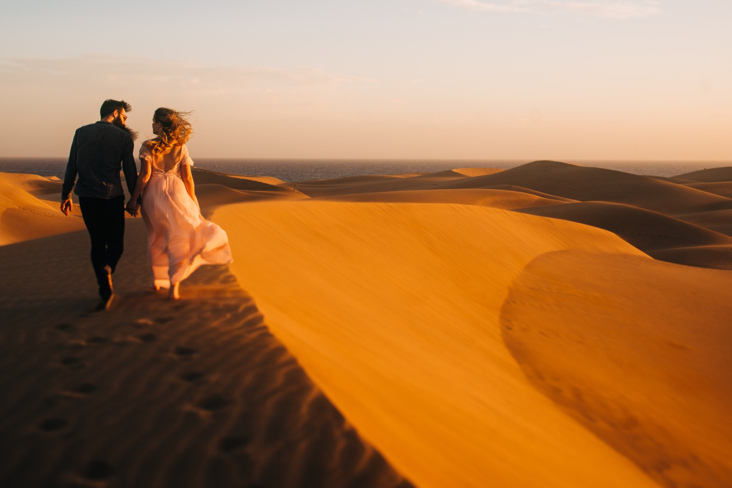 Couple walking on sand dunes in Gran Canaria showing one of the coolest places to elope in Europe.