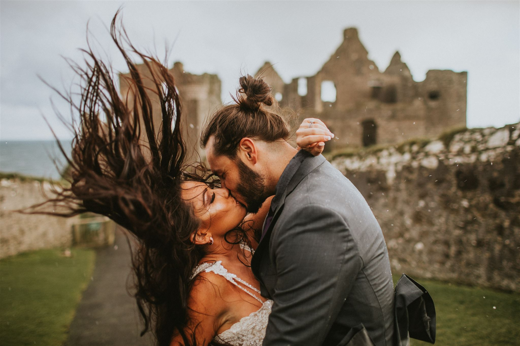 One of the best places to elope in Europe is Dunluce Castle, where this bride's long brown hair blows in the wind as she kisses her groom in front it.