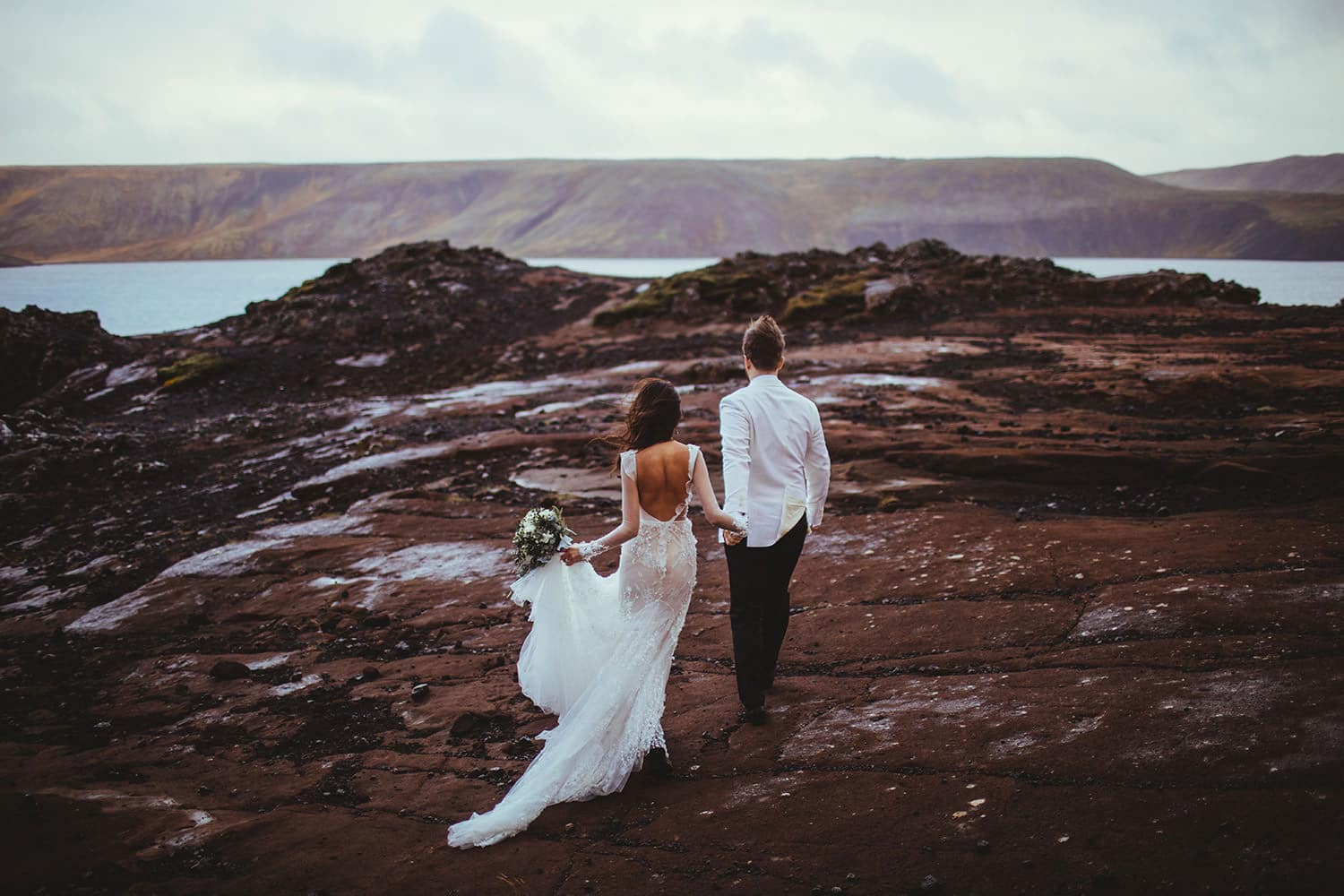 Iceland is a fantastic place to Elope in Europe as this pic of a bride and groom strolling over a lava field shows.