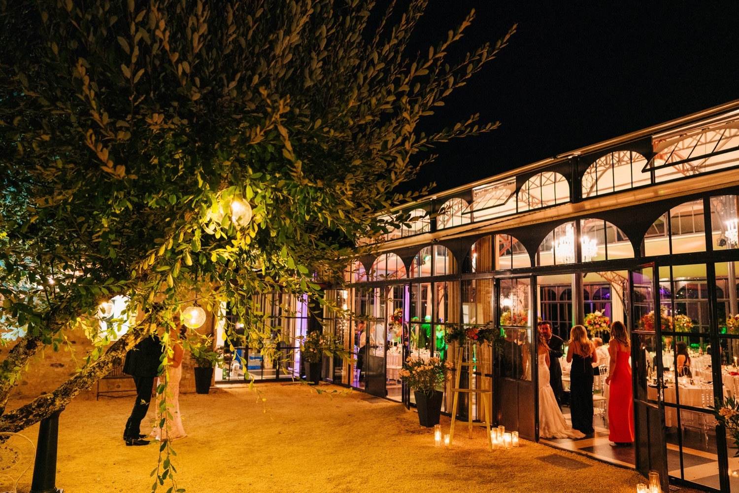 Guests celebrate in the Orangerie at Domaine La Fauconnie in France at night at a wedding reception.
