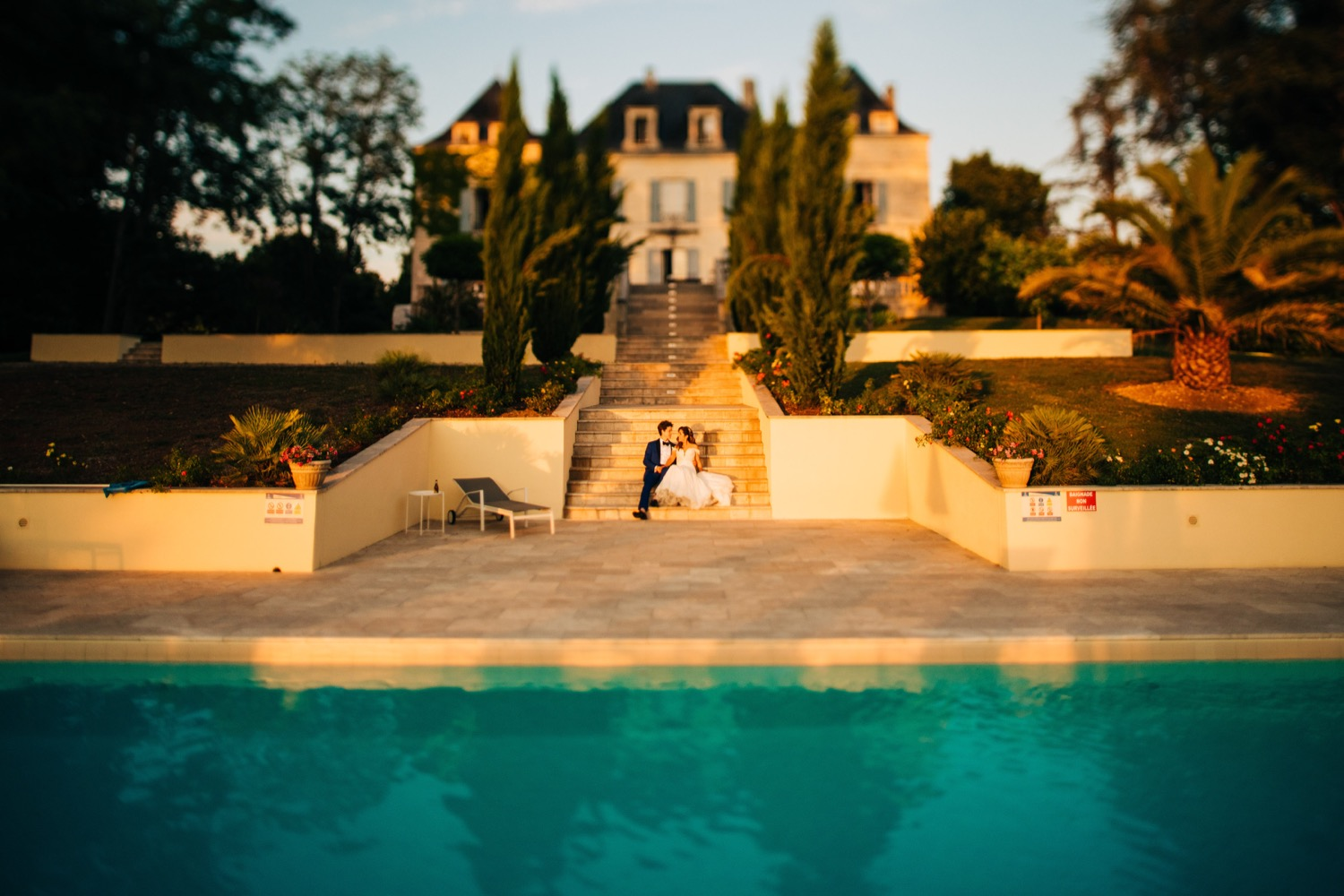 A bride and groom sit on the stairs between the outdoor pool and mansion at Domaine La Fauconnie, a wedding venue in France, as Magic Wedding Photographer takes their photo.