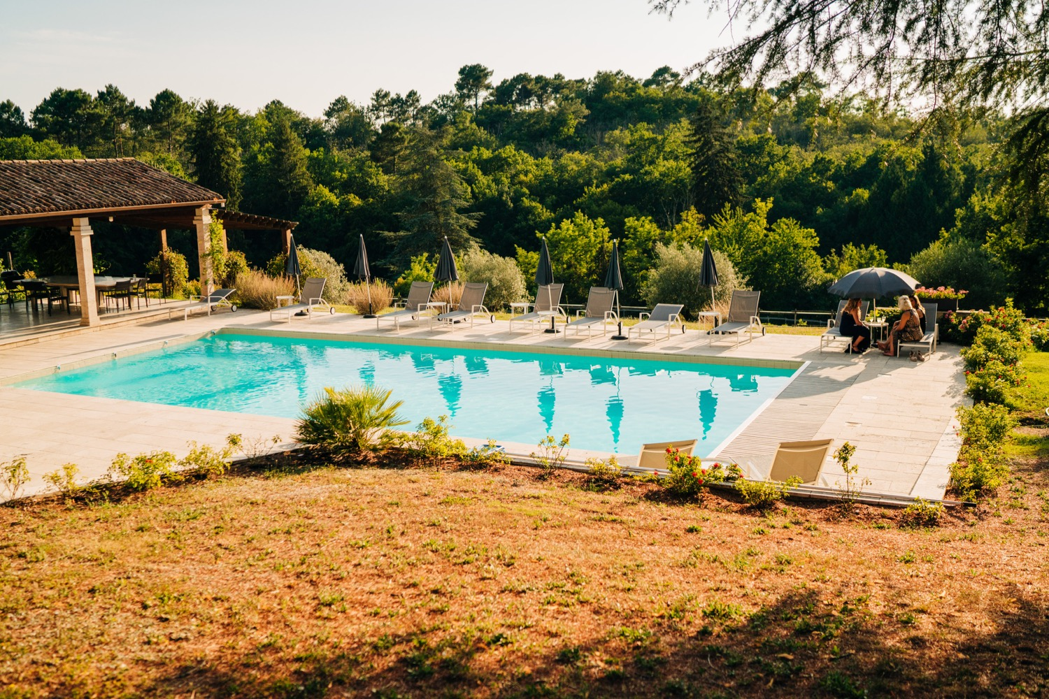 An outdoor pool surrounded by beautiful nature in France at Domaine La Fauconnie, photo captured by Magic Wedding Photographer in Europe.